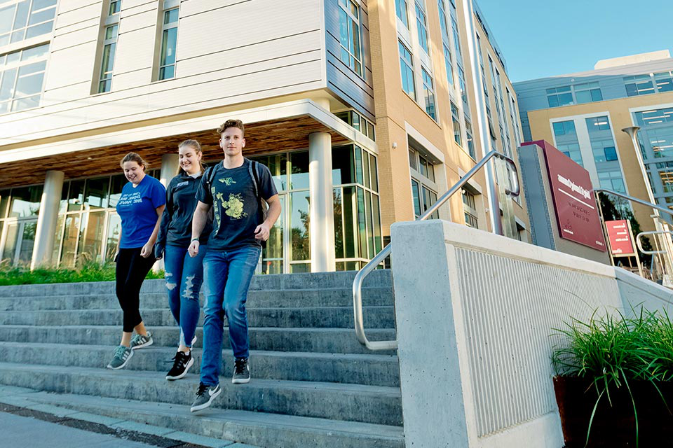 A group of students walking down the steps at the Living Learning Commons dorm
